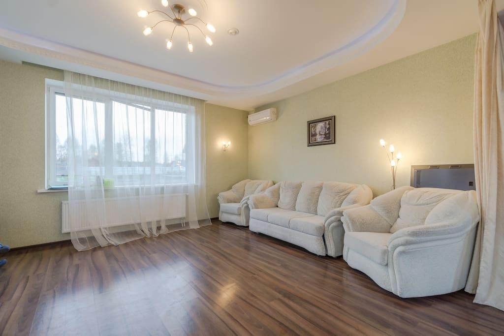 Просторная гостиная подходит для игр  с детьми или для застолья, а на ночь может стать отдельной  спальней благодаря раскладному дивану и раздвижным портьерам