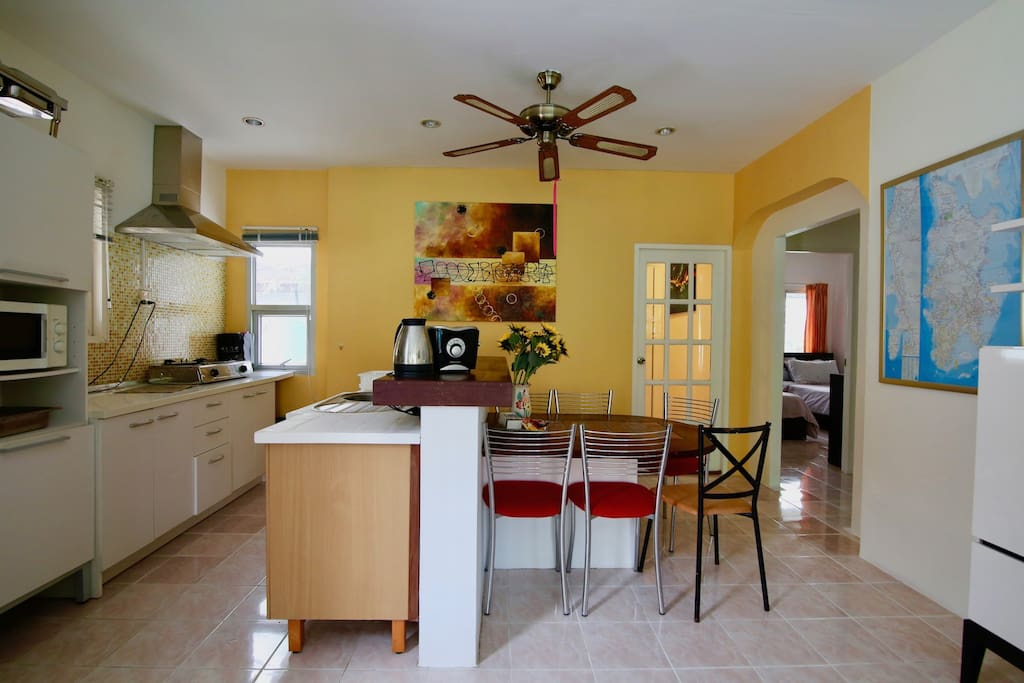 Open kitchen and indoor dining area. 3rd bedroom behind the yellow wall. Access to the other 2 bedrooms on the right.