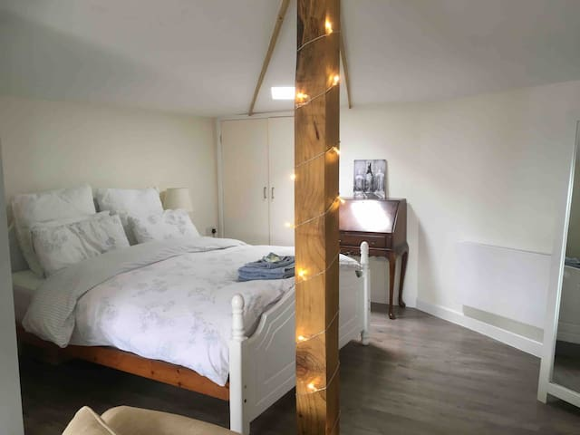 The bed has a deep filled mattress and memory foam topper. It's king size with a super king duck feather duvet in the winter and light tog in the summer. The skylight has a black out board