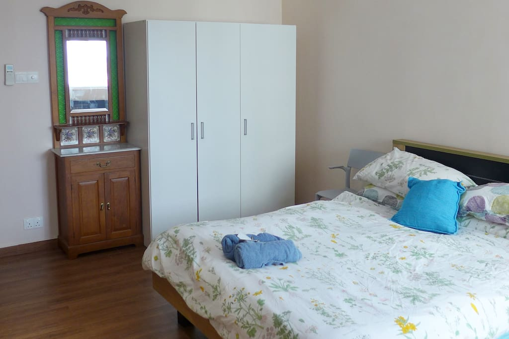 Roomy bedroom with Queen Size Bed, full wardrobe, dressing table and attached toilet