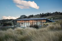 This beautiful new home, set on 12 hectares (20 acres), lies between the chic town of Wanaka and the famous Pinot Noir wineries and artists precinct near Cromwell. Each town is a 15-minute drive away but there's a historic pub and winery nearby.