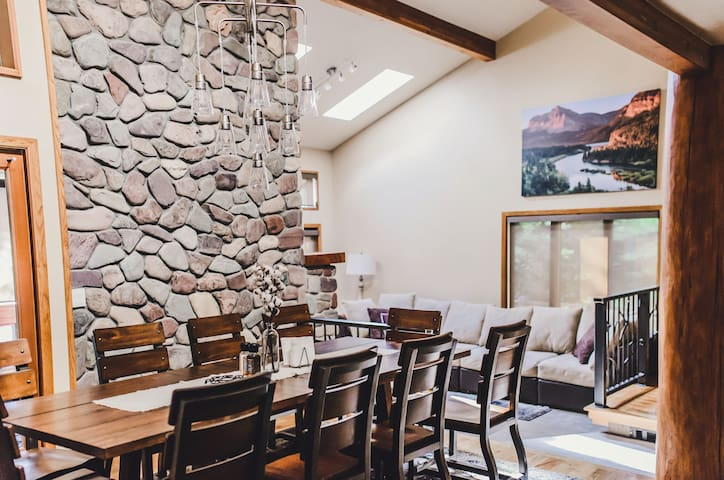 Rustic Dinning Room Table with Chandelier and Rock Feature Wall.