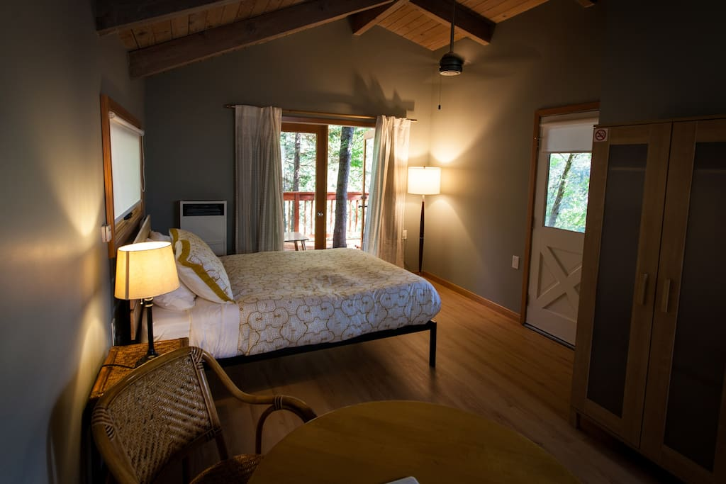 The guest cottage bedroom. French doors lead out to a deck shaded by trees.