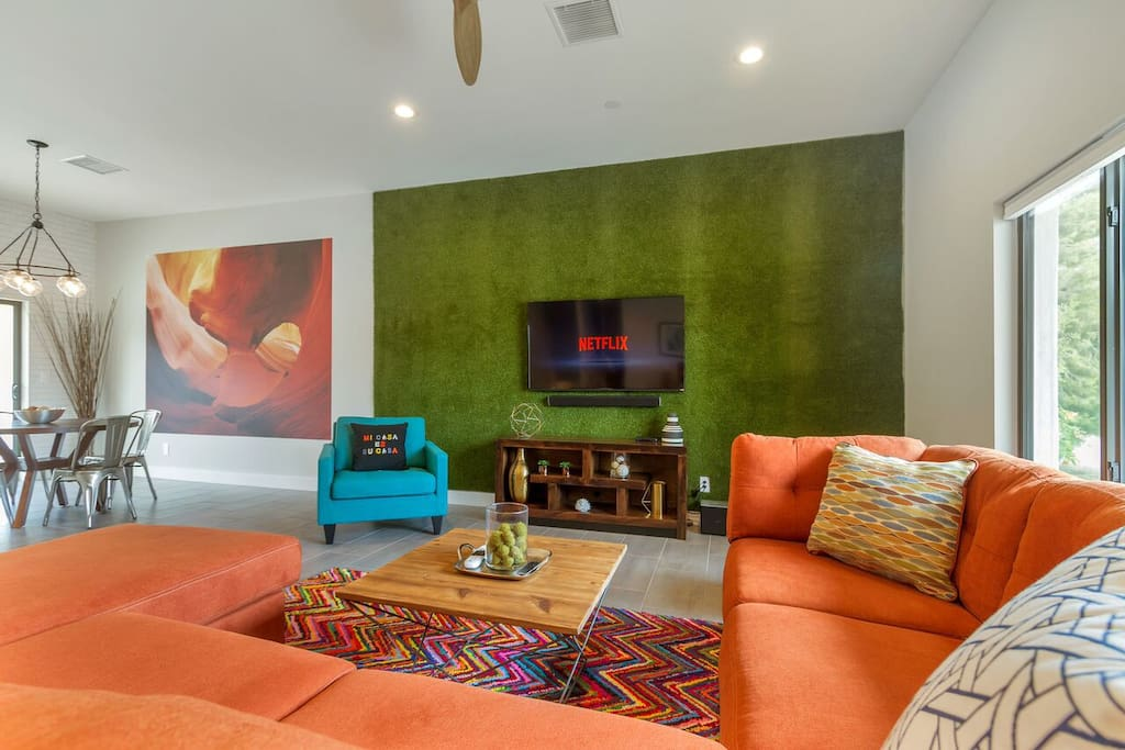 TVs all over the place, grass wall, colorful furniture make this the perfect getaway.