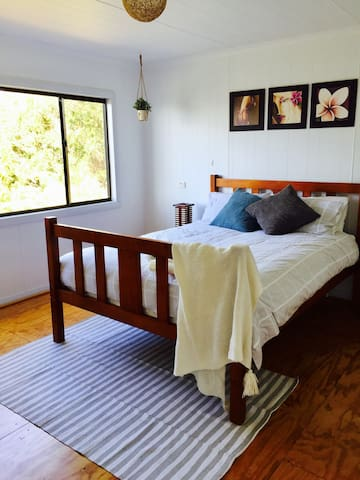 The main bedroom with queen sized bed and views to Adventure Bay and surrounding national park.