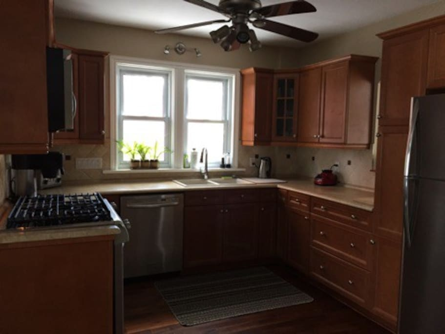 Kitchen with new Stainless Steel Appliances including fridge, gas stove, dishwasher and microwave. Double sink.