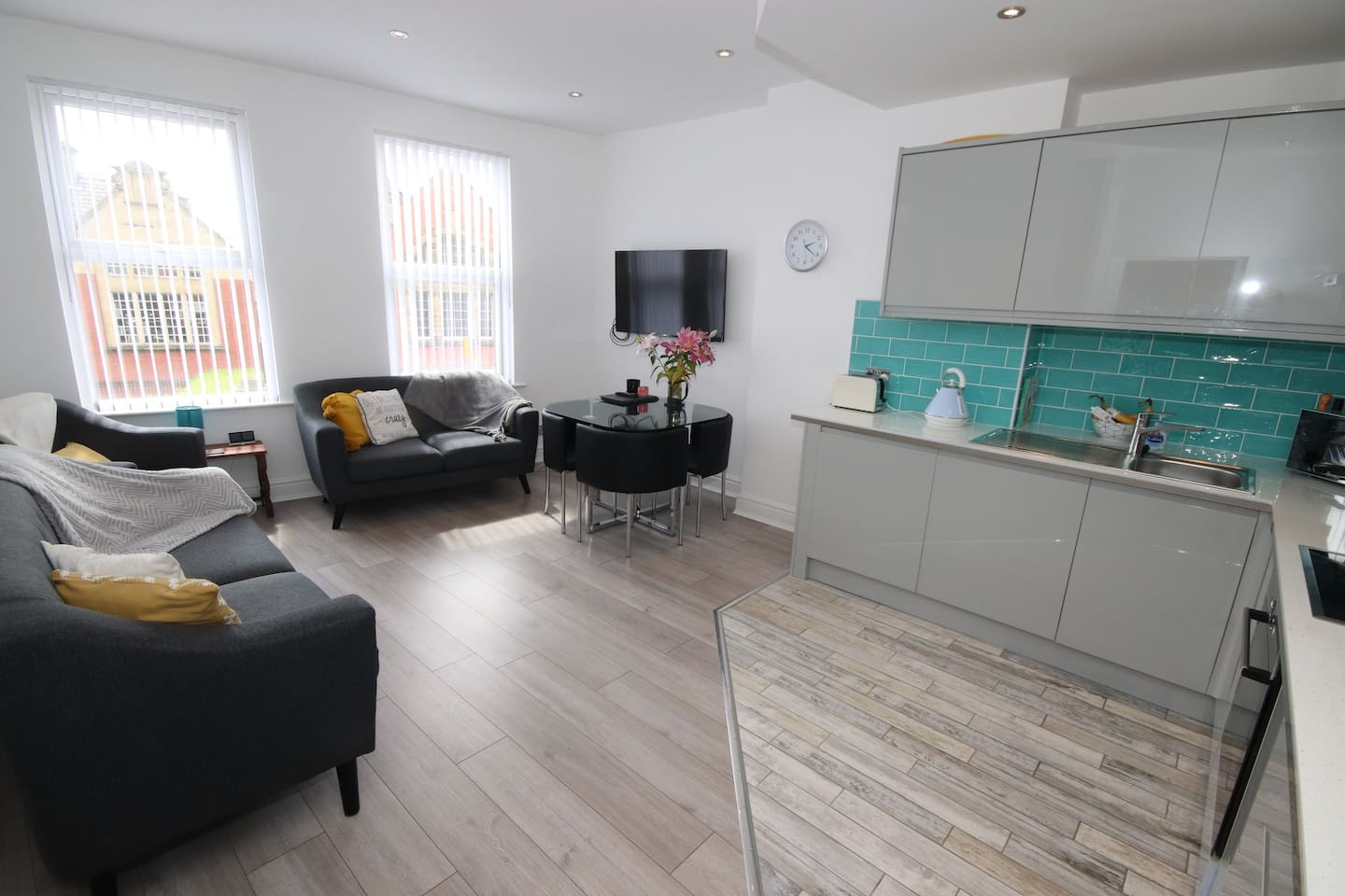 """Open-plan kitchen-livingroom, overlooking street, great view of library and council listed buildings, 50"""" flatscreen smart TV. Built-in freezer on left, fridge next to it."""