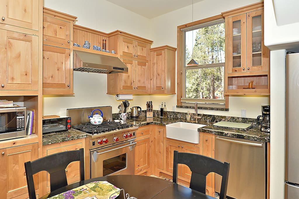 High-end stainless steel appliances, including gas range and dishwasher.