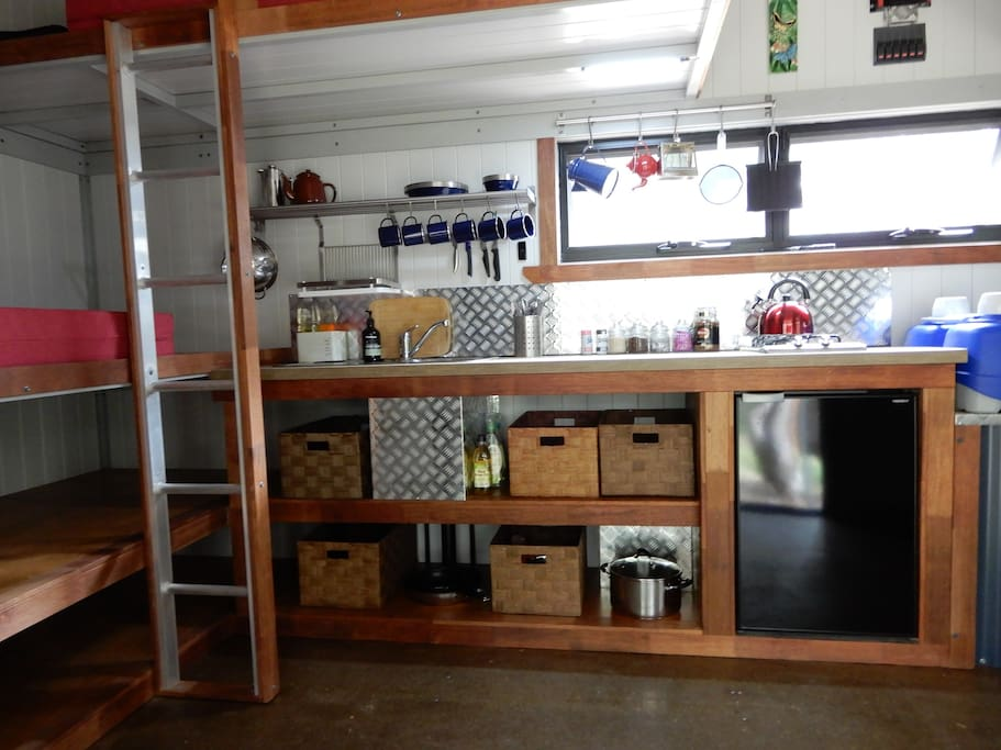 Kitchen with sink, hot/cold water, 2 burner gas hot plates, fridge.
