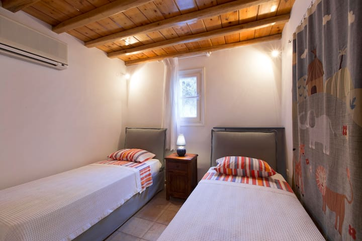 The villa's 5th bedroom has twin beds, beamed ceilings and a fun tapestry.