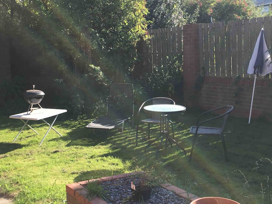 paved patio with table and chairs and grassed lawn