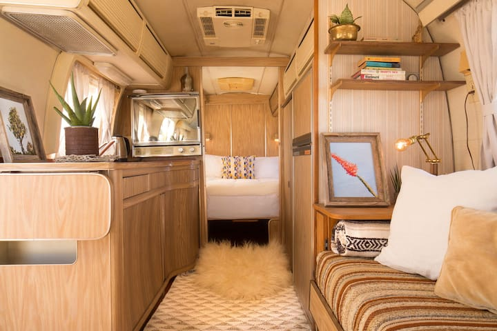 Inside of the airstream with original vintage upholstery & touches with a King Casper bed.