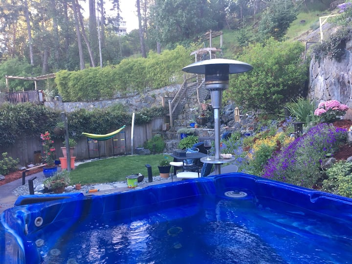 Beautiful little back yard oasis with waterfall, gardens and hot tub. House is in a neighbourhood on a quiet cul de  sac There is beautiful views of mountains from house , backs onto green space with a bluff with amazing view. Park 2mins walk away up a sh