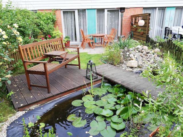 Zimmer mit großem Bett, Garten mit kleinem Teich