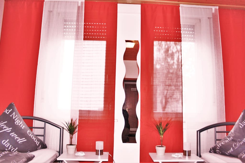 Das rote Zimmer ist mit zwei Betten, Komoden, TV, Kleiderständer, Kleiderablage und einem Schreibtisch ausgestattet