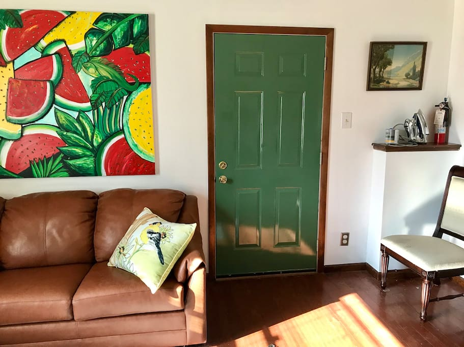This room has a couch that makes out into a bed. It hosts the tv, and a small kitchenette. It is spacious and cozy at the same time. The green door leads to the private entrance/exit direct to a patio. Notice the iron and fire extinguisher on the ledge to the right. There is a small ironing board as well.