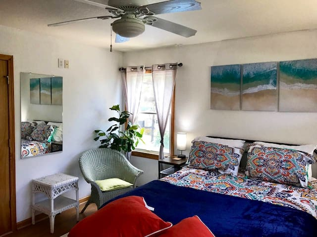 Large bedroom with new, comfy queen bed and full bathroom that includes a tub with shower .