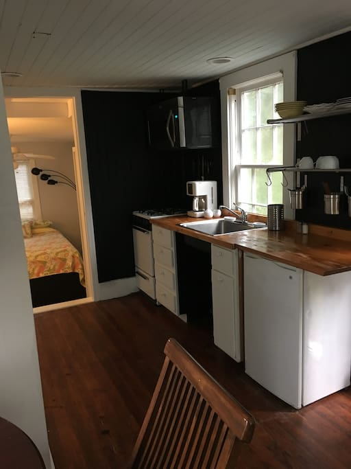 Kitchenette, directly across from the bathroom, has an apartment size stove and refrigerator, coffee maker, microwave.