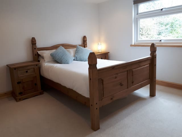 Comfortable double bedroom to rear of the house. View of rustic garden surrounded by trees.