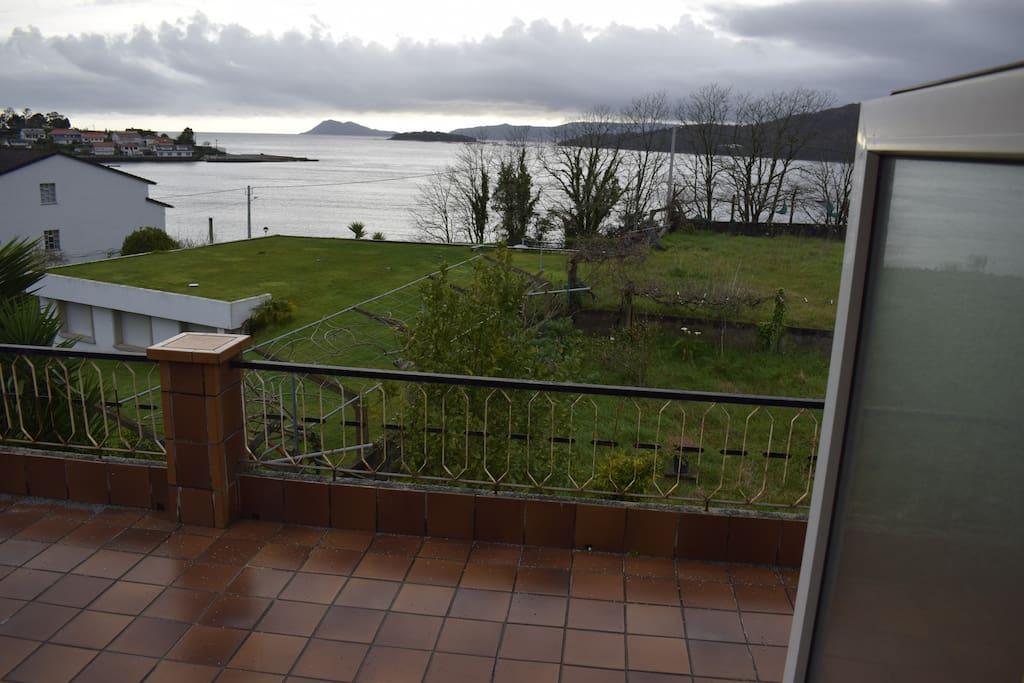 Terraza con toldo y mesa para comer fuera, viendo el mar