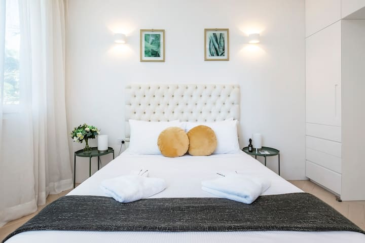 The bedroom features a double bed, ample built-in storage space, and lush linen curtains. With triple-glazed doors and windows throughout, enjoy a good night's sleep in complete peace and quiet.