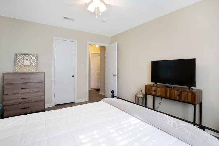 Master bedroom with queen bed, smart tv, closet and dresser