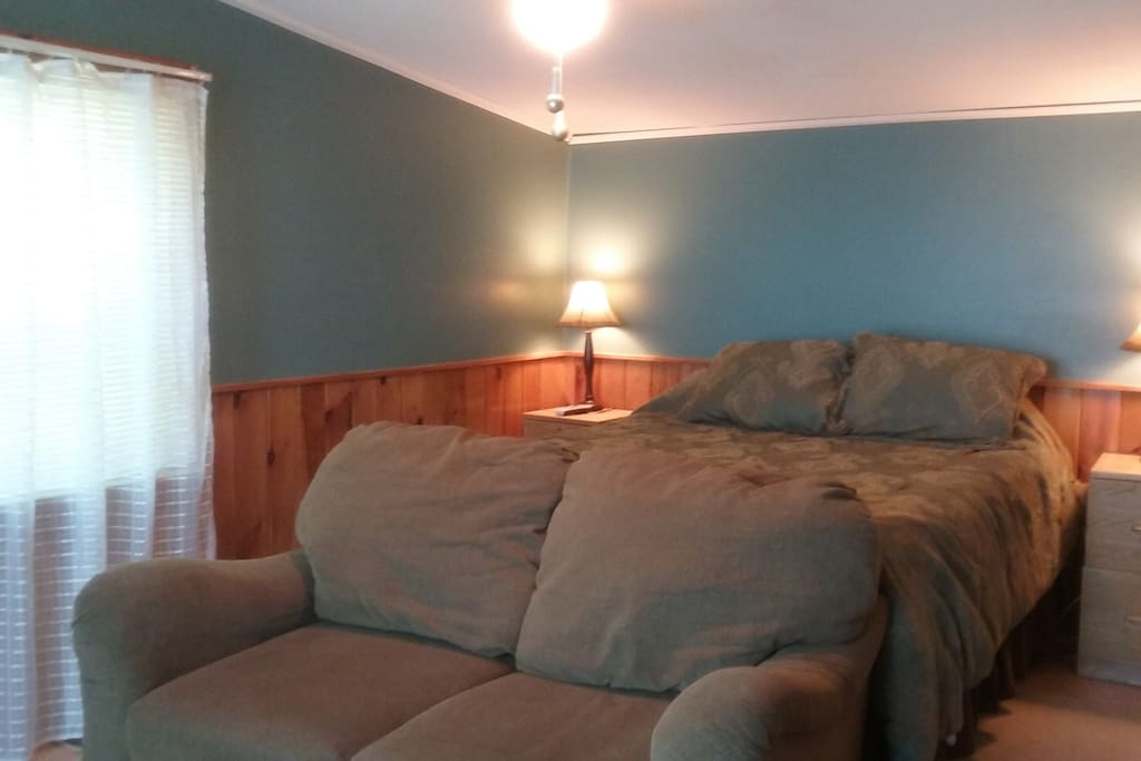 Your private bedroom with loveseat, coffee table,  tv and stereo.