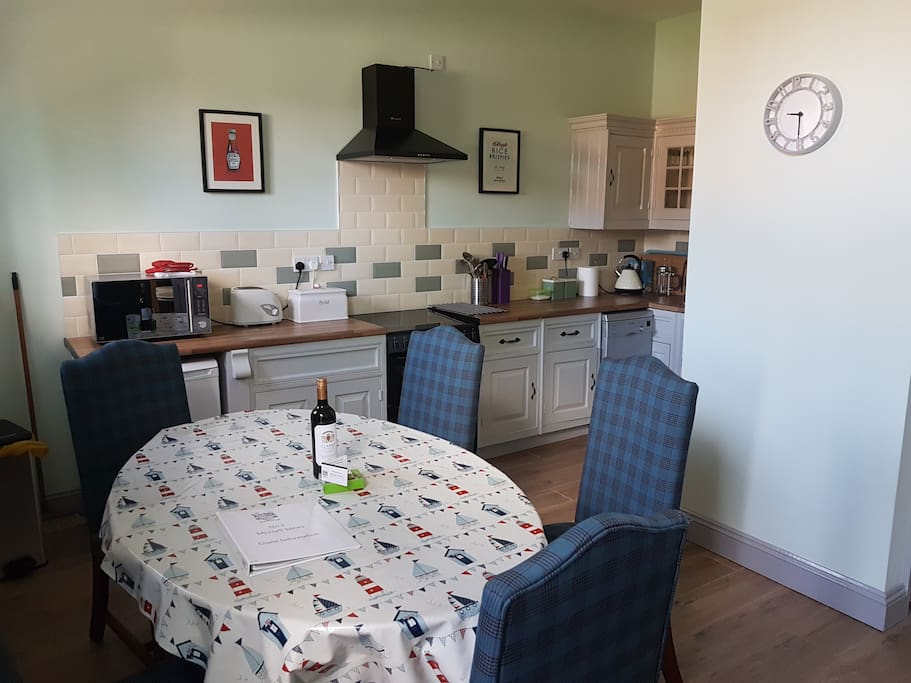 A fully equipped kitchen with oven, hob, extractor, fridge and slimline dishwasher.
