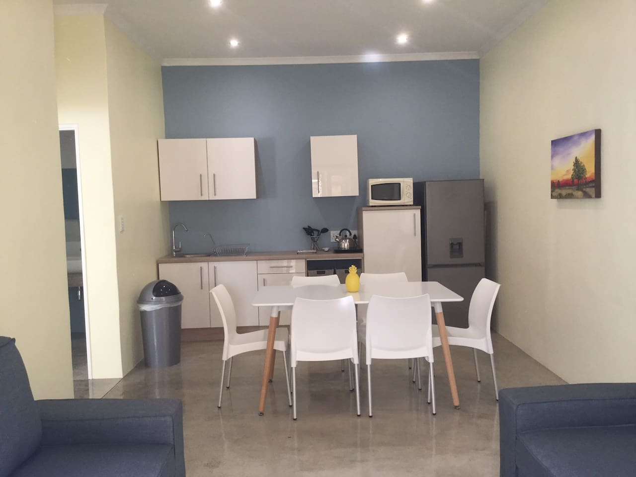 Living area with kitchen, dining table and two sleeper couches
