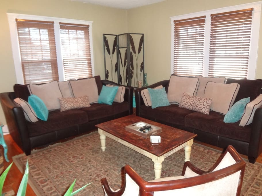 Welcome home to a cozy living room with plenty of seating and even a dog bed for our furry guests!
