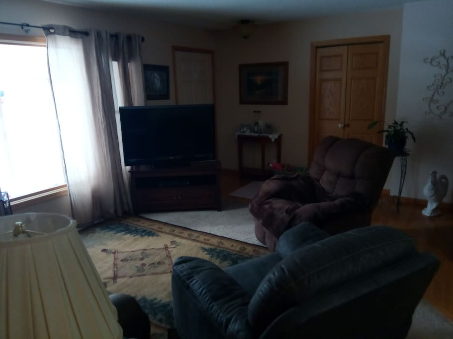 Living room with TV and four recliner chairs