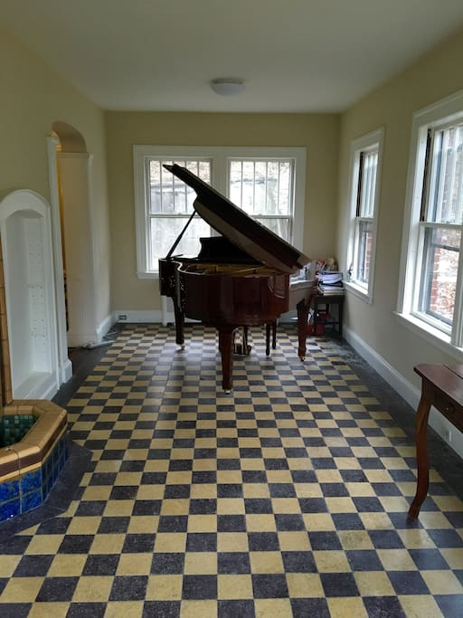 Enclosed sun room with grand piano and violin