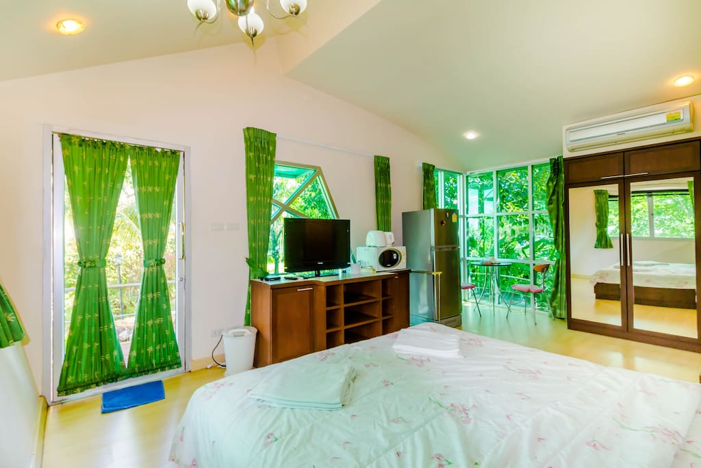 The view of the room inside fronting the garden and with sitting area in the corner