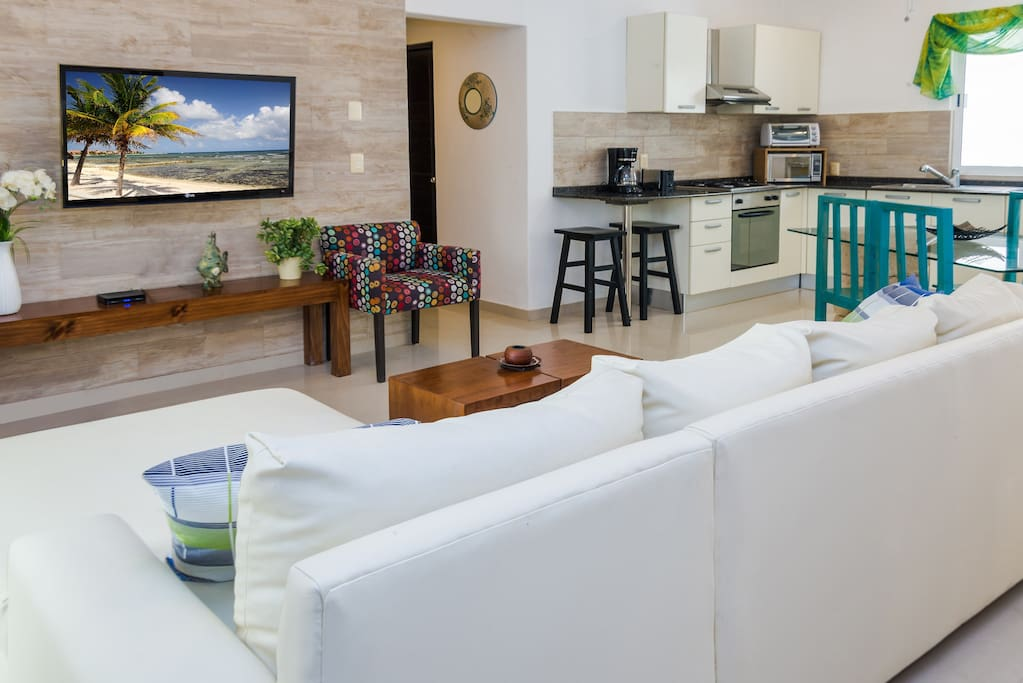The living room has a large flat screen TV with cable service with as well English as Spanish channels. There is lounge seating for 4 people. A fully-equipped kitchen has a large dining table with also seating for 4.