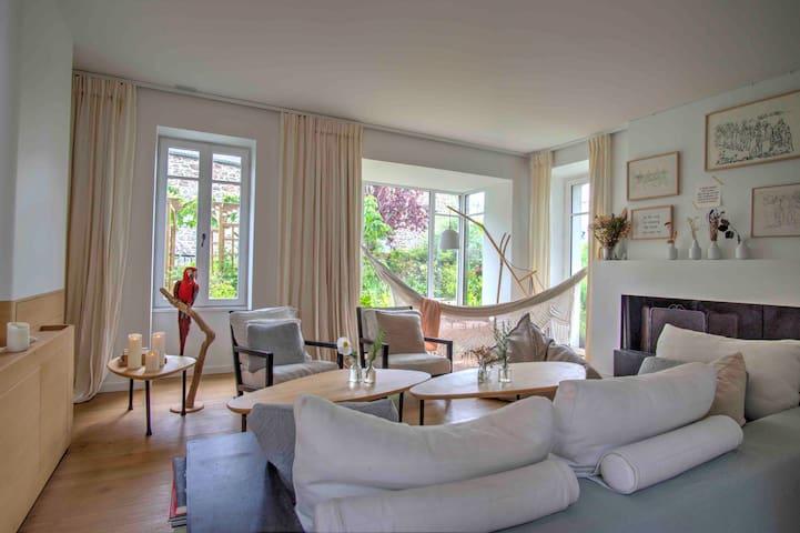 Vue générale du salon, avec le meuble TV à gauche, le bow window avec hamac donnant sur le jardin, la cheminée à droite
