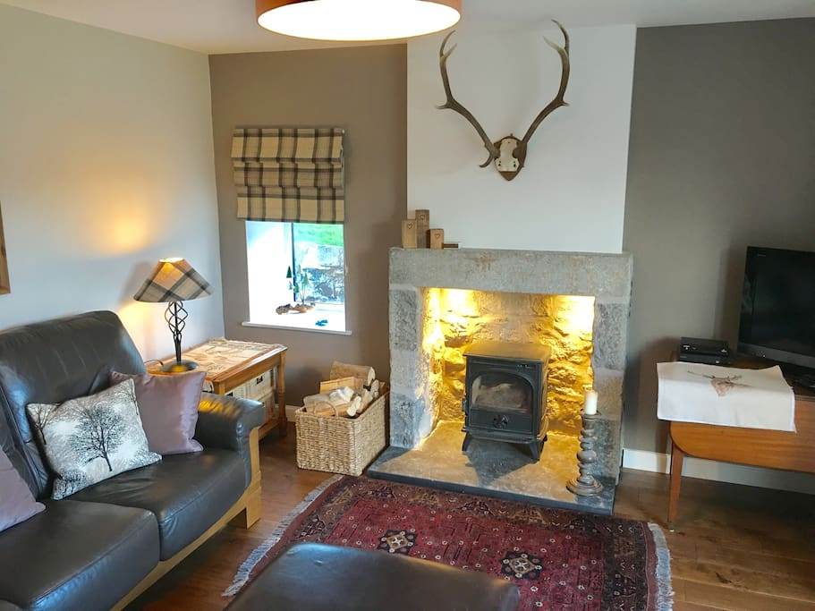 The new living room with wood burning stove & bright patio doors into the enclosed garden.