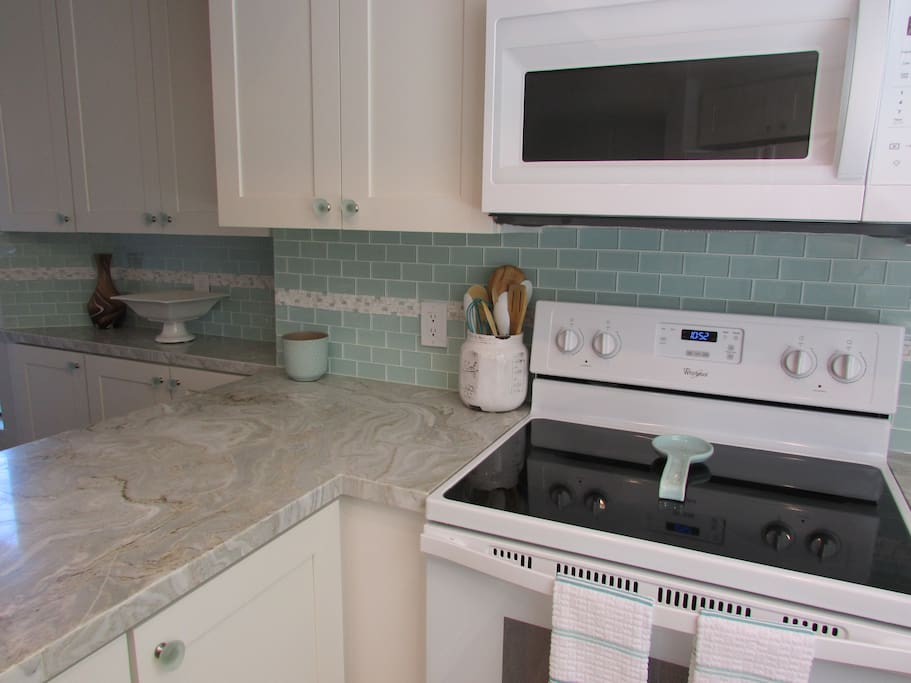Beautiful glass subway tile back splash. Stone counters. Gorgeous!  Light and Bright!