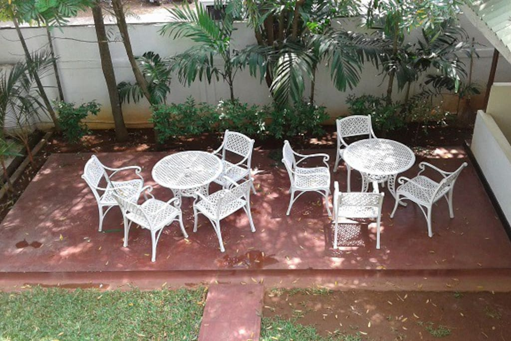 there are table and chairs out in the garden