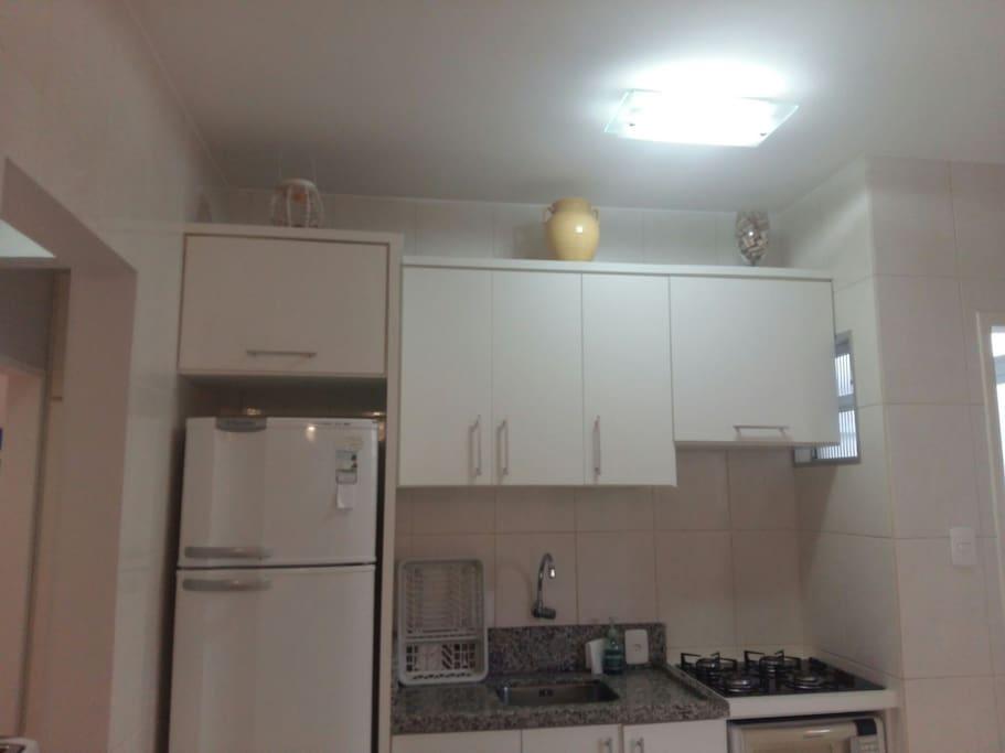 cozinha completa com cooktop, geladeira, forno microondas, forno elétrico , louças e panelas.