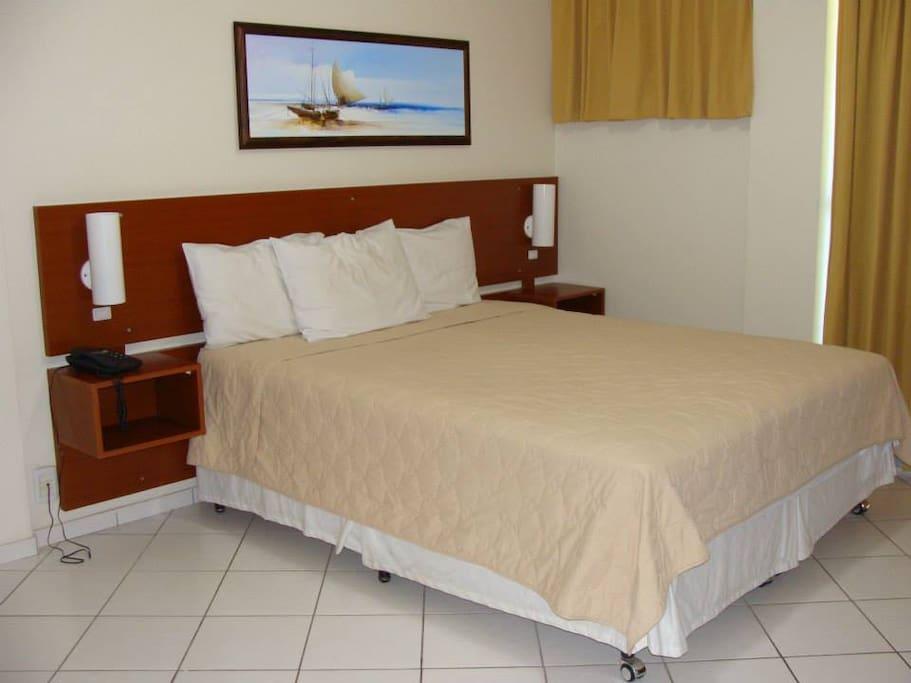 Suíte com cama box de casal, tv, luminárias, quadro decorativo, frigobar, ar condicionado, armário, mesa de apoio, cadeira e banheiro privativo