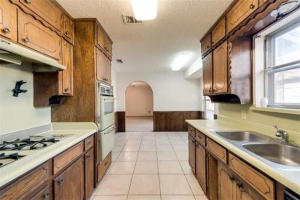 Large kitchen right off living room overlooking the backyard. Coffee pot, fridge, dishwasher, oven, broiler,  has range and microwave.