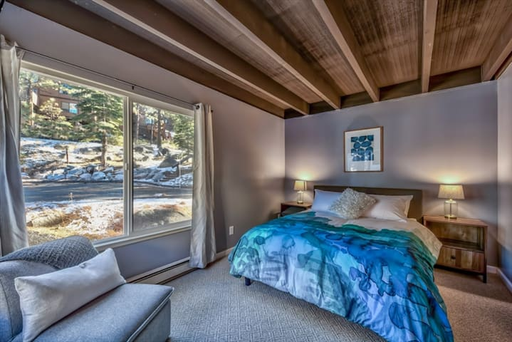 Master Queen bedroom with rustic wood furnishings cool and vibrant tones.