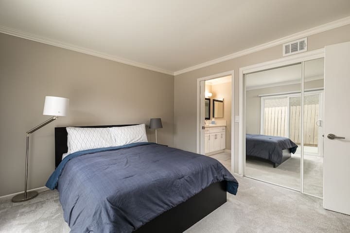Master bedroom with mirrored wardrobe and walk-in closet
