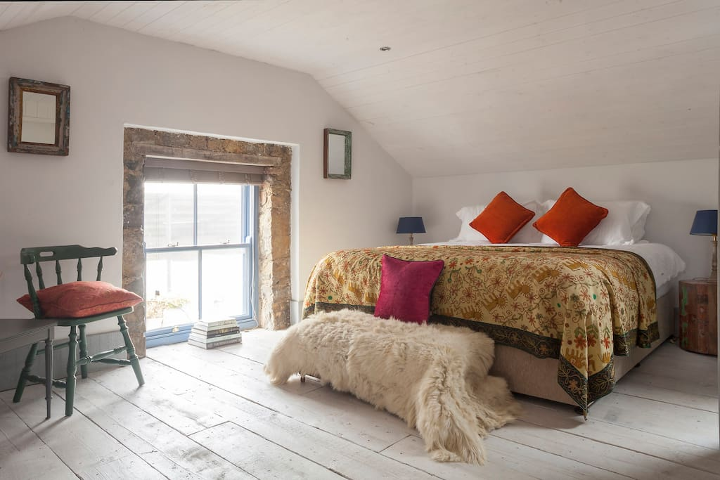 The bright hayloft room, complete with superking size bed, exposed stone features and reclaimed, painted wooden floorboards.