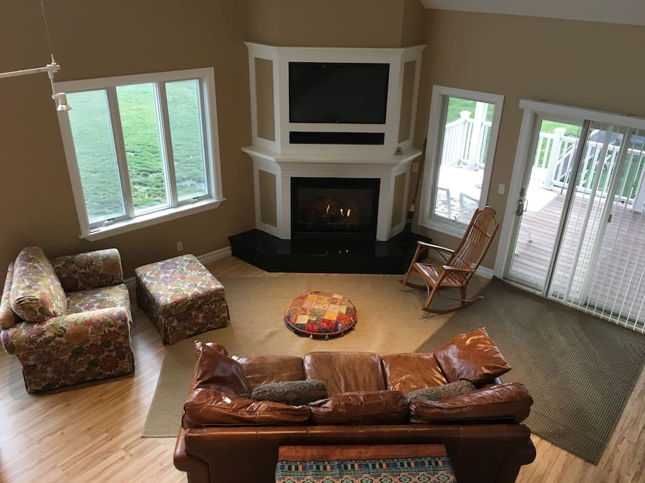 Living room with gas fireplace, smart tv, bluetooth speaker, and super comfy double chair and leather couch.