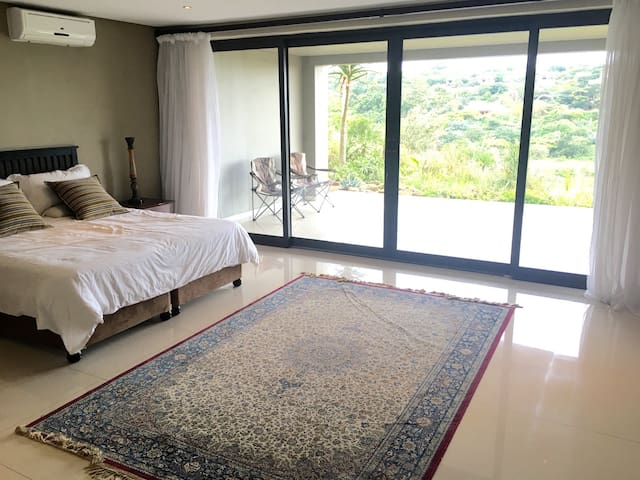 A large patio off this bedroom, with views across the golf course to the sea.