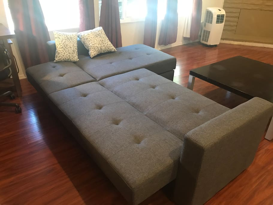 sofa bed in living room. Push the back to the front then pull back to un-fold the sofa