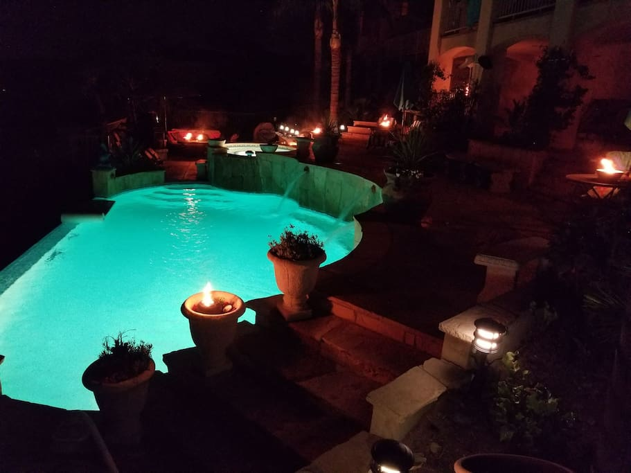 Pool and surroundings illuminated with TIKI fires lit.