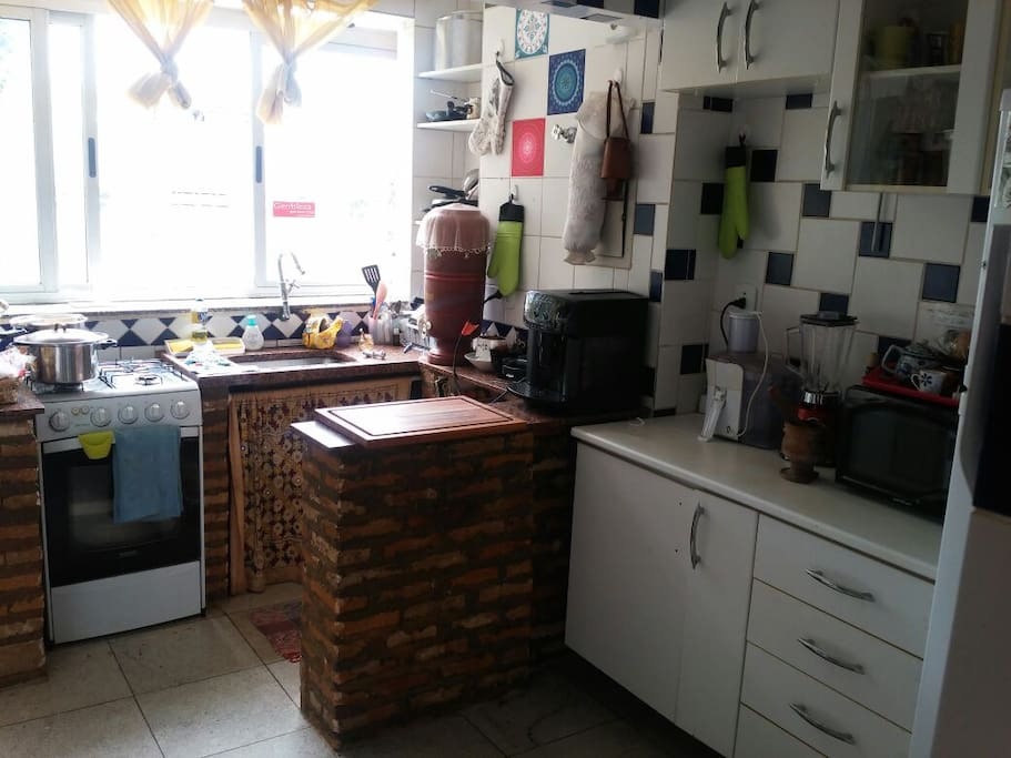 Cozinha ampla e bem iluminada, como tudo que precisa para cozinhar e comer (inclusive taças para vinhos e eletrodomésticos).