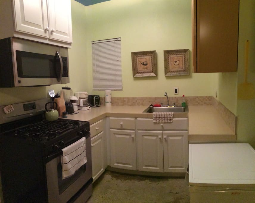 Small kitchen but full-size appliances with gas oven stove and and above oven microwave.